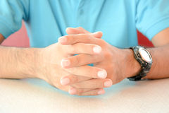 A man sitting with clasped hands on the table Royalty Free Stock Images