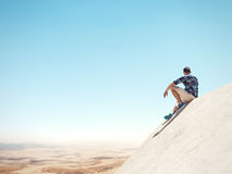 Man sitting on a cliff and desert Stock Photography