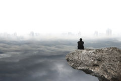 Man sitting on cliff with gray cloudy sky cityscape background. Businessman thinking and sitting on cliff with gray cloudy sky cityscape background Royalty Free Stock Images