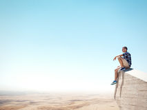 Man sitting on a cliff and looking at the desert Stock Images