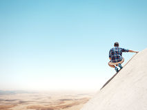 Man sitting on a cliff and looking at the desert Stock Photo