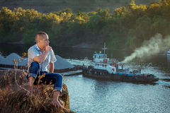 Man sitting on the cliff Stock Image