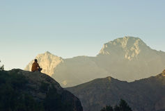 Man sitting on a cliff at sunset surrounded by mountains Stock Image