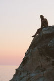 Man sitting on cliff top on the sunset Royalty Free Stock Photo