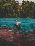 Man Sitting and Closing Eyes on Teal Bench Royalty Free Stock Image