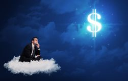 Man sitting on a cloud dreaming of money. Caucasian businessman sitting on a white fluffy cloud wondering about huge money sign stock photo
