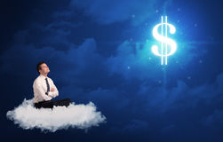 Man sitting on a cloud dreaming of money. Caucasian businessman sitting on a white fluffy cloud wondering about huge money sign stock image