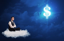 Man sitting on a cloud dreaming of money. Caucasian businessman sitting on a white fluffy cloud wondering about huge money sign royalty free stock images