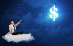 Man sitting on a cloud dreaming of money. Caucasian businessman sitting on a white fluffy cloud wondering about huge money sign royalty free stock photos