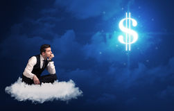 Man sitting on a cloud dreaming of money. Caucasian businessman sitting on a white fluffy cloud wondering about huge money sign stock photos