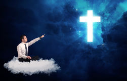 Man sitting on cloud lokking at a cross Royalty Free Stock Images