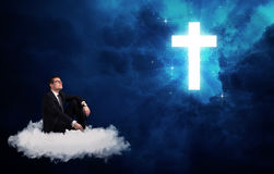 Man sitting on cloud lokking at a cross Royalty Free Stock Photos