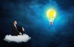 Man sitting on cloud looking at a lightbulb Stock Images