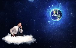 Man sitting on cloud looking at planet earth. Caucasian businessman sitting on a white fluffy cloud looking and wondering at planet earth Royalty Free Stock Photos