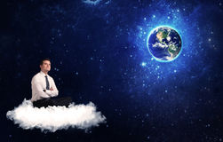 Man sitting on cloud looking at planet earth Royalty Free Stock Photo
