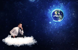 Man sitting on cloud looking at planet earth Stock Photos