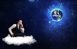 Man sitting on cloud looking at planet earth Stock Images