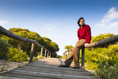 Man sitting on a coastal boardwalk. Man sitting on the rustic wooden railings of a coastal boardwalk crossing the dunes and beach sand, as he relaxes and enjoys Stock Photo