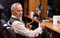 Man sitting with cognac glass and cigar. Business owner. Side view portrait of handsome senior man looking forward while sitting on armchair with cognac glass royalty free stock image