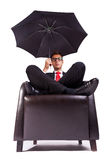 Man sitting in comfortable armchair with umbrella Royalty Free Stock Photos