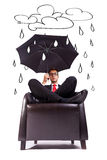 Man sitting in comfortable armchair with umbrella Stock Image