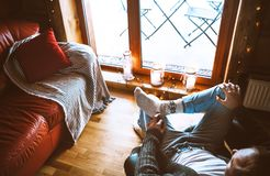 Man sitting in comfortable chair opposite big window in cozy country home. Countryside vacation concept top view image stock image