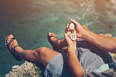 Man sitting with compass above the ocean on cliff. Man sitting with compass above the ocean Stock Photos