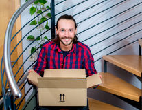 Man sitting in corridor and opening a package Stock Images