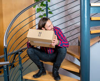 Man sitting in corridor and opening a package Royalty Free Stock Image