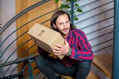 Man sitting in corridor and opening a package Royalty Free Stock Photos