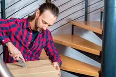 Man sitting in corridor and opening a package Royalty Free Stock Images