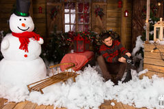 Man Sitting on Cotton Snow Decor Holding Skates Stock Images