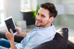 Man sitting on couch with digital tablet Royalty Free Stock Photo