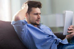 Man sitting on couch with digital tablet Royalty Free Stock Photos