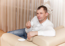 Man sitting on the couch drinking a cup of coofee Stock Image