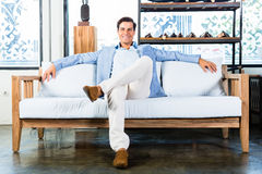 Man sitting on couch in furniture store Royalty Free Stock Images