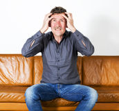 Man sitting on couch Stock Image