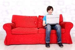 Man sitting on couch with laptop Stock Photos