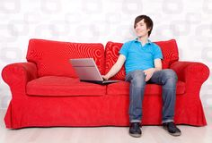 Man sitting on couch with laptop Royalty Free Stock Photo