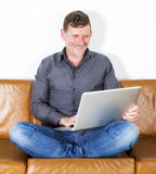 Man sitting on couch with laptop Stock Images