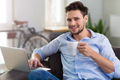 Man sitting on couch with laptop Royalty Free Stock Images