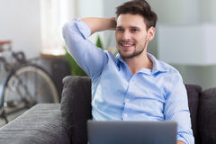 Man sitting on couch with laptop Stock Photo
