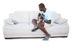 Man sitting on couch learning to play guitar with his tablet pc Stock Photo