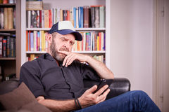 Man sitting on couch in living room looking on mobile phone broo. Ding, pondering and looking seriously Royalty Free Stock Image