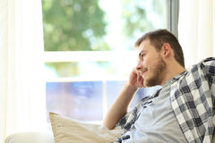 Man sitting on a couch and looking through a window Stock Photography