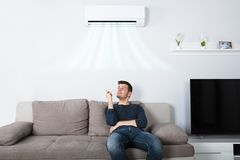 Man Sitting On Couch Operating Air Conditioner. Young Happy Man Sitting On Couch Operating Air Conditioner With Remote Control At Home stock photography