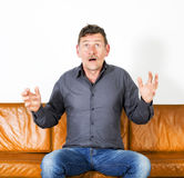 Man sitting on couch Stock Photo