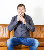 Man sitting on couch Stock Photos