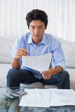 Man sitting on couch working out his finances Royalty Free Stock Photography