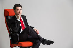 Man sitting with crossed legs. Caucasian businessman sitting on red sviwel chair with his legs cross and hand at chin Stock Images